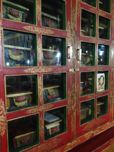 Glass faced case holding fabric and wooden Buddhist prayer books at Likkir gompa/monastery, north of Leh, Ladakh.