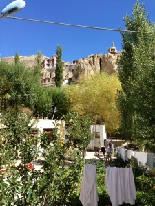 A modest view across the guesthouse's courtyard, looking up to the monastery  through trees and a clothes line.