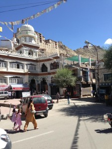 An Indian woman wearing a kurta walks her children across the busy corner of the main square in Leh in front of the mosque, with Leh Palace in the background and Tsemo Fort even further up.