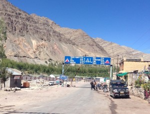 "Clearing a passport check in Upshi, looking back north towards Leh, posted ""49km"""