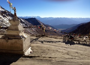 Prayer flags and a chorten mark the general top of Chang La. A BRO marker is a bit further along.